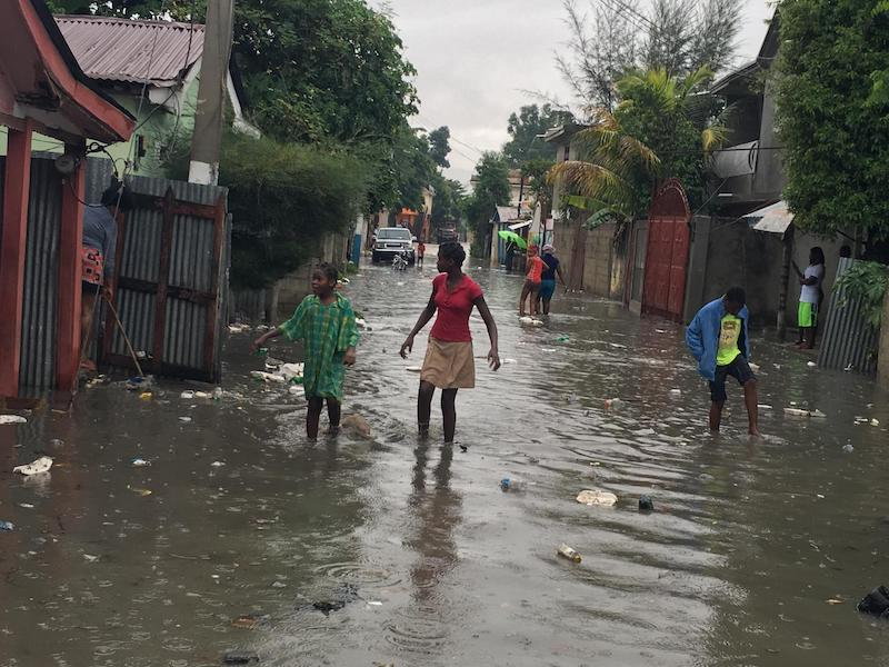 Women and children wade through a street in Hinche, Haiti as Hurricane Irma approaches, September 7, 2017.