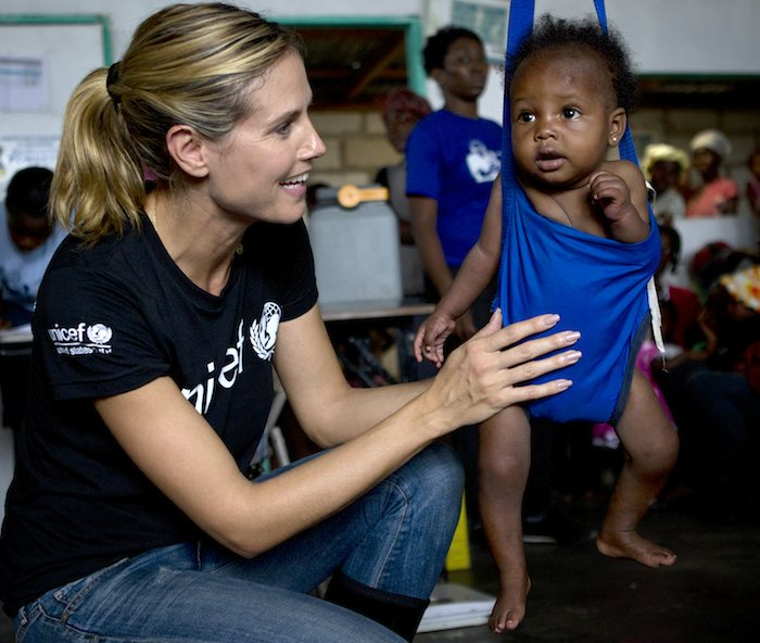 UNICEF Supporter Heidi Klum visits a UNICEF health clinic in India and weighs a baby to help protect her from malnutrition.