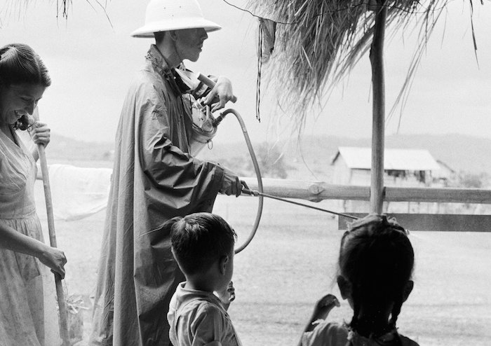 In 1958 in the Guayaquil coastal region of Ecuador, a malaria campaign worker sprays the outside of a house with UNICEF-supplied insecticide to kill the malaria-bearing mosquito.