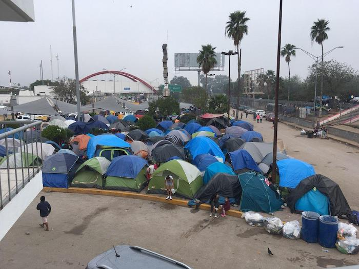 In December 2019, families seeking asylum in the U.S. live in a tent encampment in Matamoros, Mexico near the red-arched port of entry building, visible in the distance.