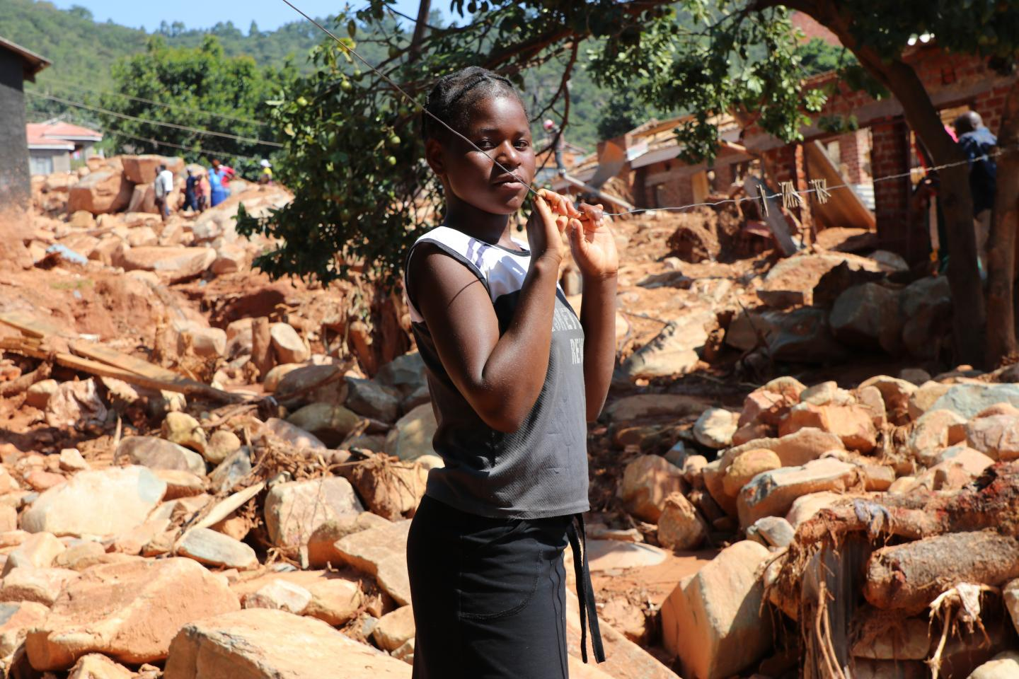 Praise stands among what used to be her neighborhood in Ngangu Township. Most houses have been completely buried by the rocks that tumbled down the mountain when Cyclone Idai hit. ©UNICEF Zimbabwe/Elizabeth Mupfumira