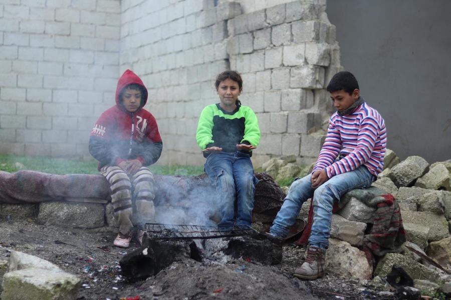Mohammad, 13, (right) and his sister Mehdia, 9, gather around a fire to warm up with their neighbor Sami.