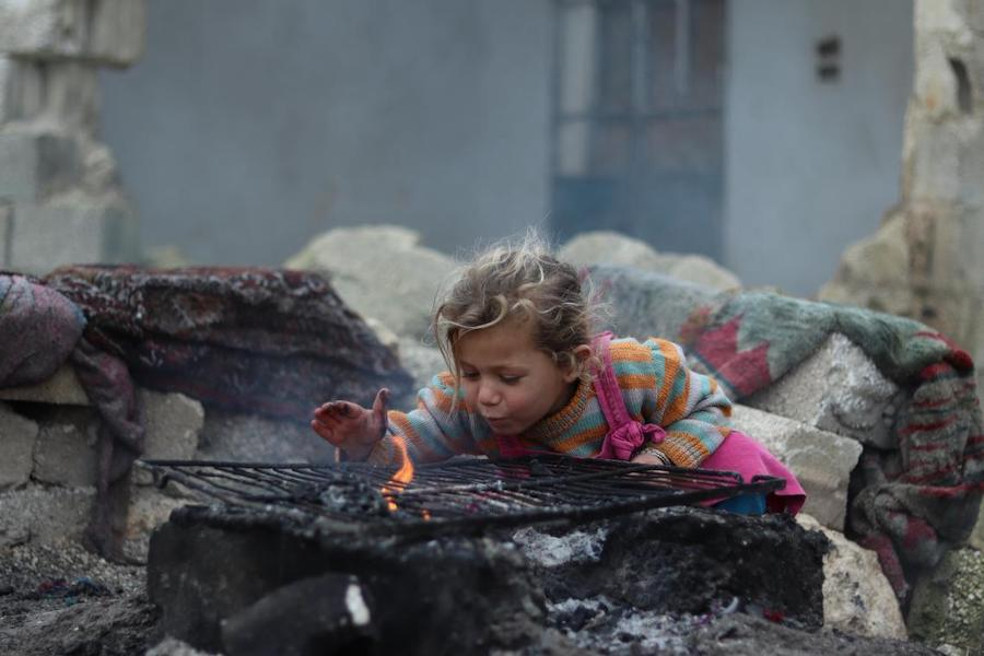 Khudr Al- Issa Mountaha, 3, warms her hands over the fire in front of their one-room home in Karm Al- Nazha neighborhood of east Aleppo. Photo: UNICEF/ Syria 2018/