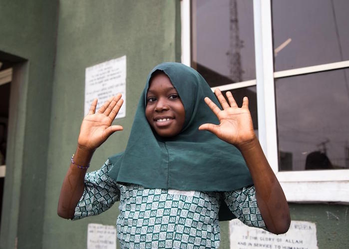 In Lagos, Nigeria, a girl shows her clean hands after learning how to wash them properly at a UNICEF-supported COVID-19 public awareness event in March 2020.