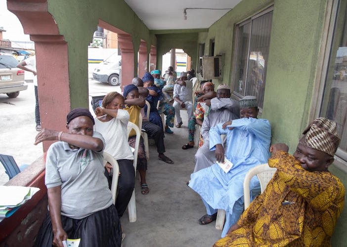 At a UNICEF-supported COVID-19 public awareness in Lagos State, Nigeria in March 2020, participants practice coughing into their elbows to avoid spreading the novel coronavirus.