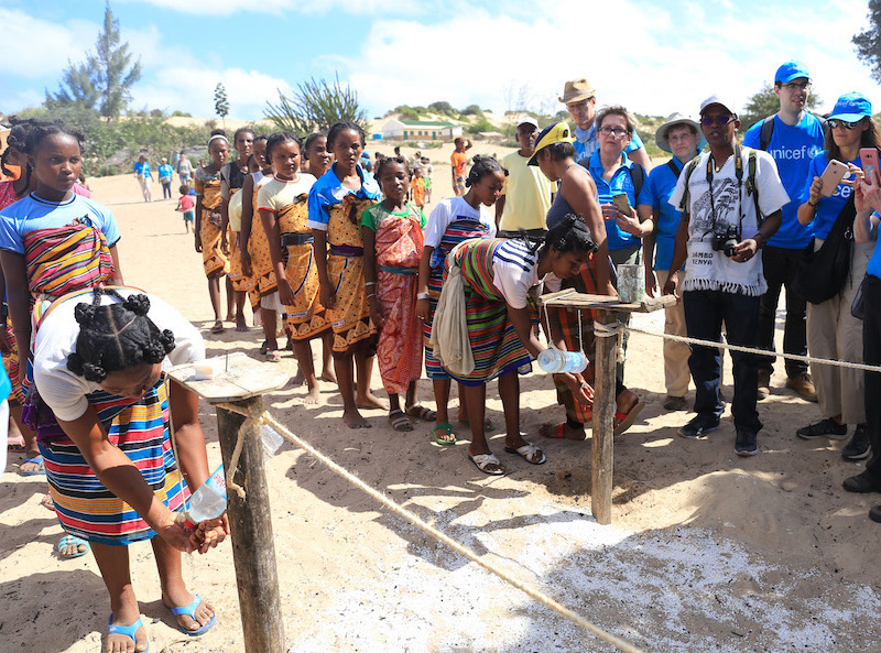 Mother Leaders wash hands with ash before a celebration welcoming a delegation from UNICEF USA and Zonta International in Tanandava, Madagascar.