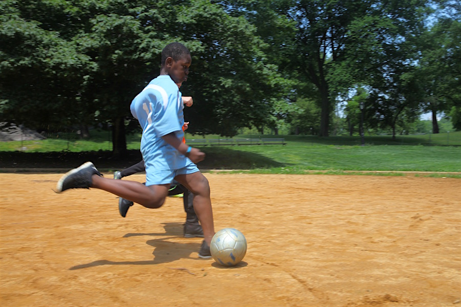 Ibrahim, with David alongside, shoots downfield during Field Day soccer.