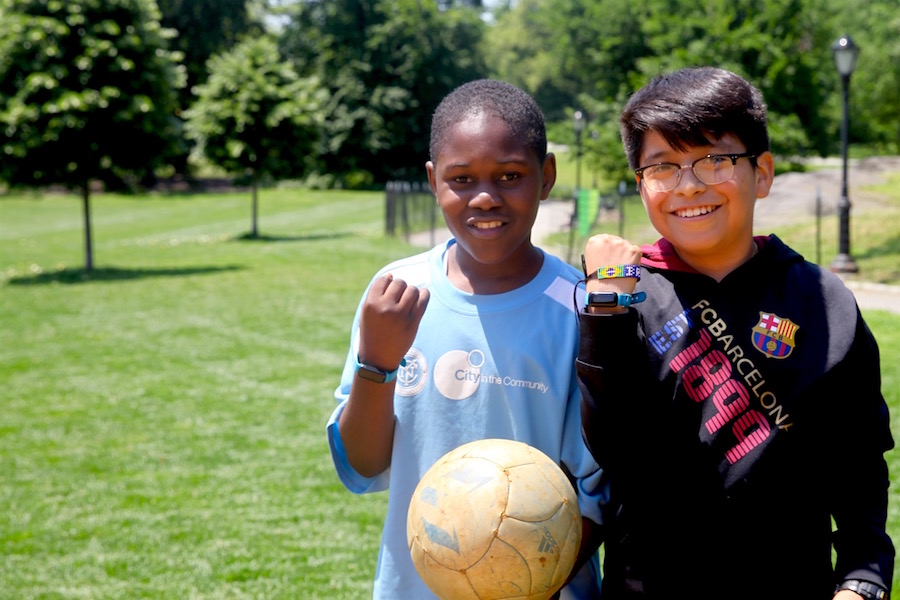 Ibrahim and David show off their UNICEF Kid Power Bands during Lexington Academy's Field Day in Central Park's East Meadow.