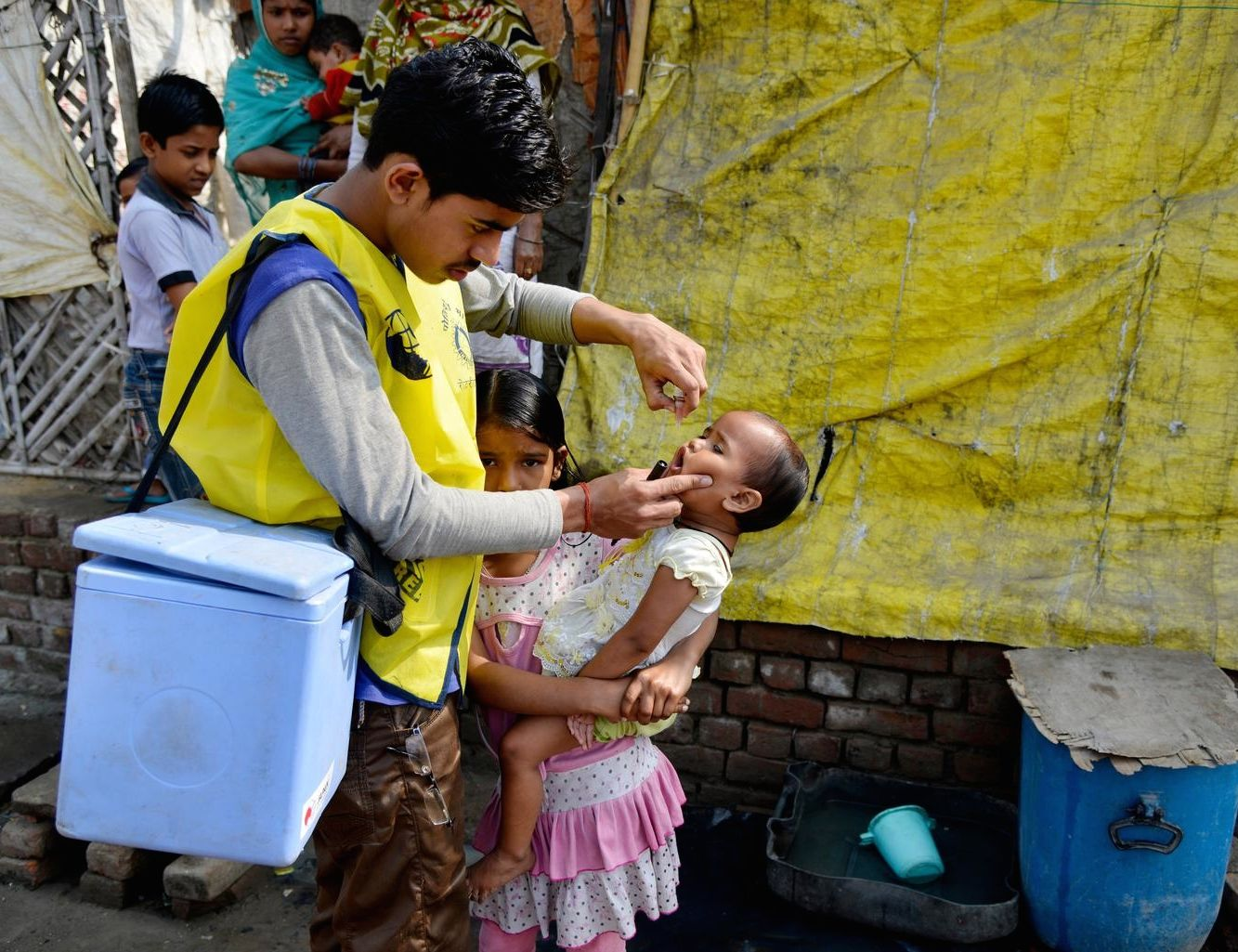 A vaccinator in India, where poor sanitation heightens the risk of childhood diseases, immunizes a child