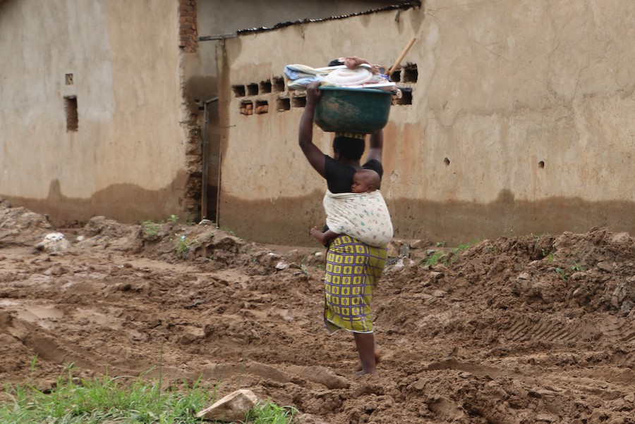 On January 29, 2019, a woman carries a basin full of the household goods she was able to salvage after her house was flooded in Bujumbura, Burundi.