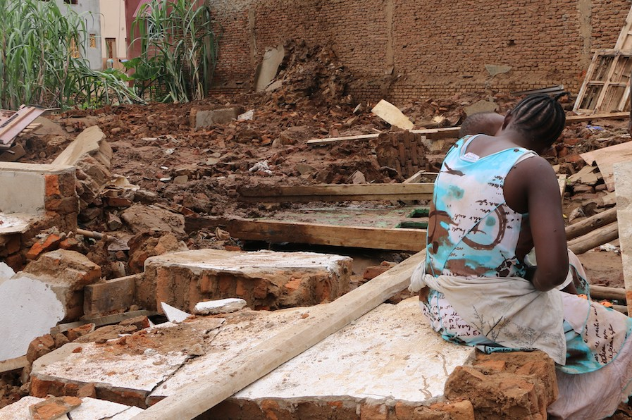 On January 29, 2020, a young mother sits in the ruins of her house, destroyed by heavy flooding in Burundi.