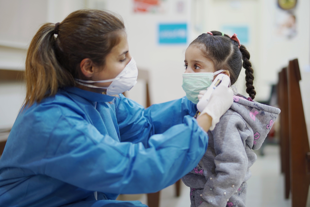 A masked health care worker takes the temperature of a masked child, in a Lebanon clinic