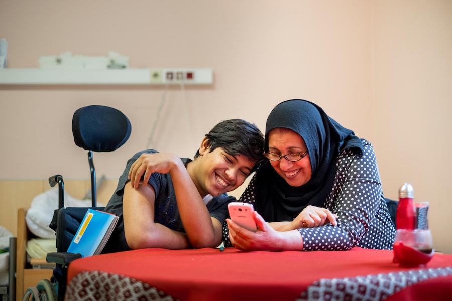 Sajad, 16, takes a break from his German homework to watch a video his mother in September 2017. Refugees from Iraq, they live in an abandoned senior citizens hospital in Vienna.