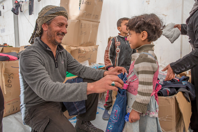 Mohammed buys winter clothes provided by UNICEF for his daughter, Sidra, 4, in Hasahsham camp, Iraq.