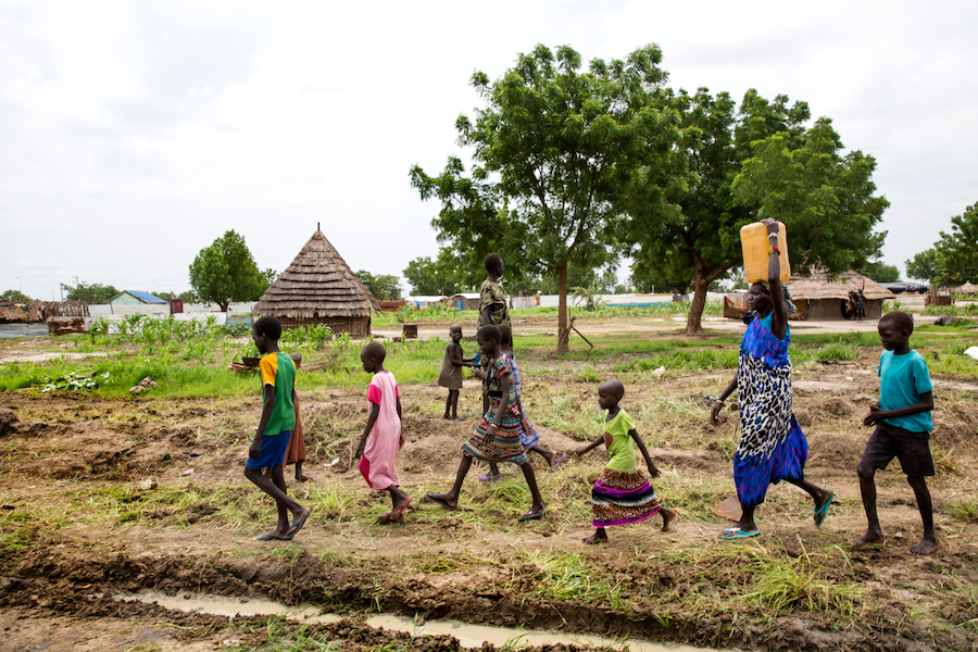 Angelina Nyakuma (second right) walks with children as she carries a jerry can of safe drinking water, drawn from a water pump at the Machakos Primary School, Bentiu, South Sudan, July 2017.