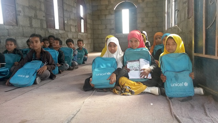 Third grade students, aged between 8 and 10, who received school bags from UNICEF, sit in a temporary classroom in Taiz, Yemen in March 2017.