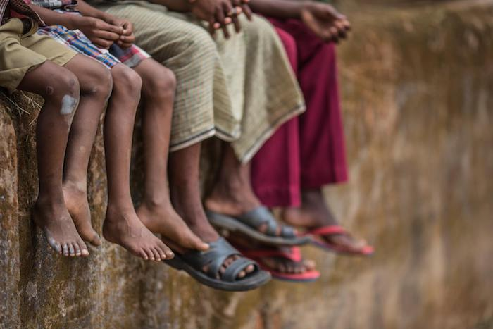 Children and adults sit on a wall in Chhattisgarh, India. UNICEF is implementing The Lion Project to help improve the lives of institutionalized children in Chhattisgarh and seven other states.