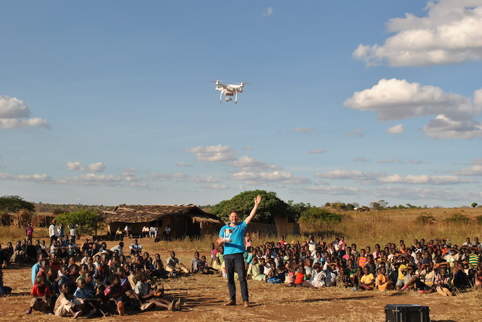 Locals observe UNICEF's Drone Corridor Lead Michael Scheibenreif as he pilots an unmanned aerial vehicle in the UNICEF supported test corridor in Malawi.