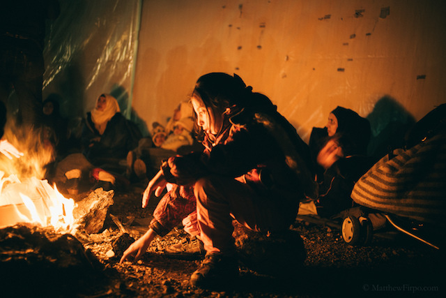 Refugees staying warm on the shores of Greece.
