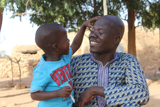 Moussa, 4, and his father, Hama, outside their home in Songho village, central Mali.