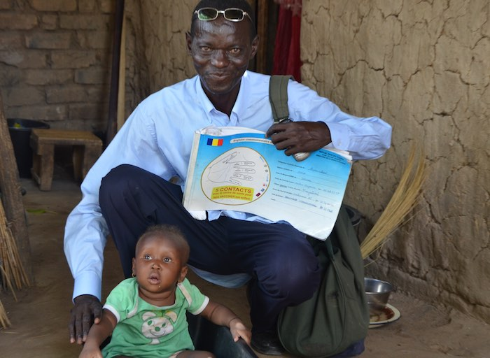 A community relay member reviews a child's vaccination status using the community register in Sarh, Chad
