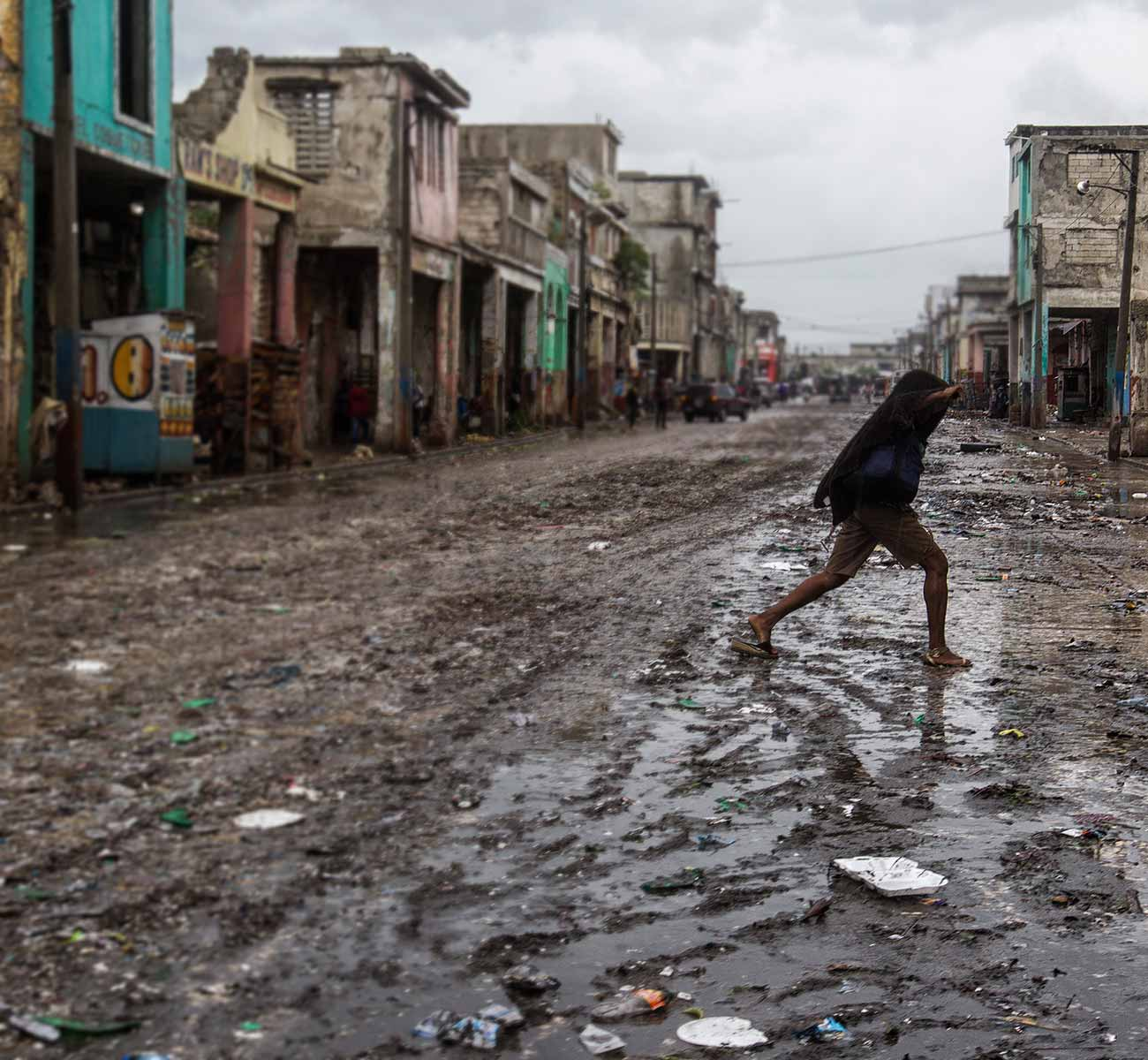 A Haitian boy in slippers crosses an unpaved road littered with mud and debris, and lined with ruined buildings - Donation form background