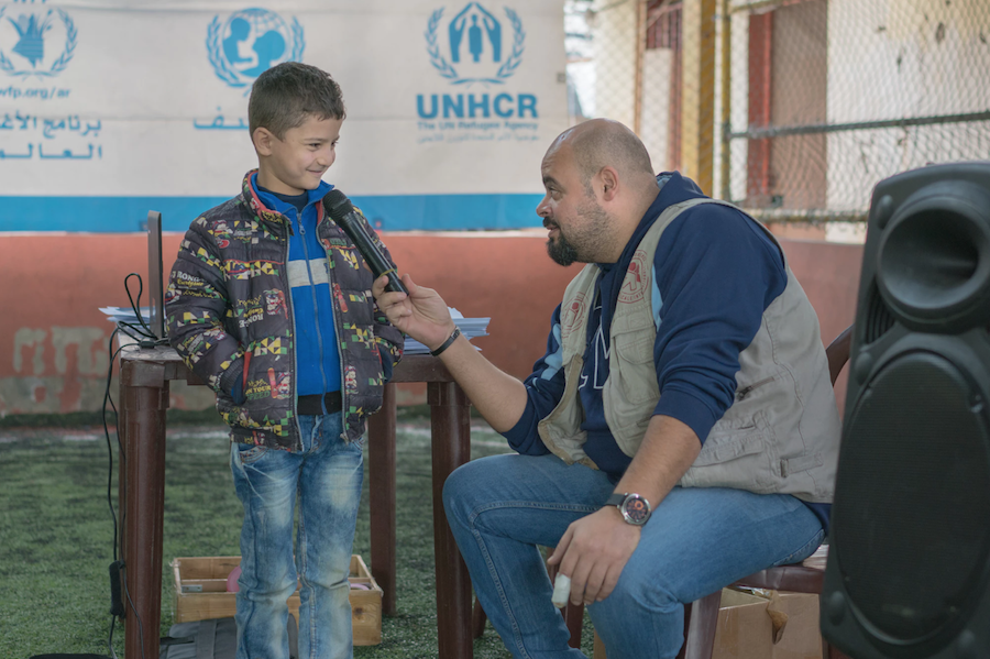 Ali Cherro, right, from UNICEF partner PU-AMI Lebanon, answers questions about the LOUISE common card, which helps refugees access the benefits for which they are eligible.