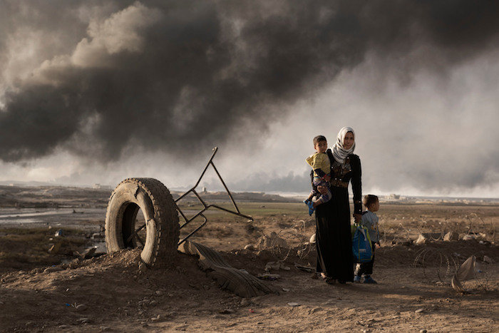 A displaced woman walks with two children south of Mosul, Iraq in 2016.