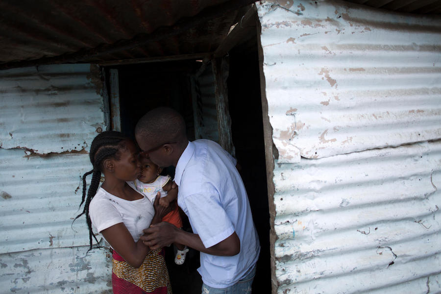 Einosio, 24, a fecal sludge operator, says goodbye to his wife, Aida, and their 6-month-old daughter, Melucha, in Maputo, Mozambique in September 2017.
