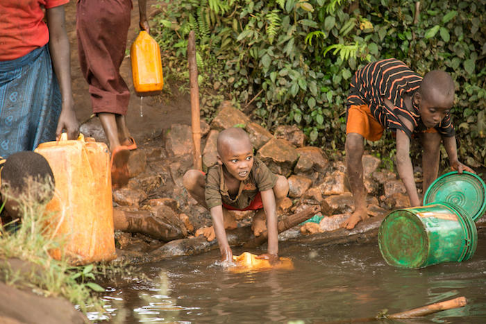 Children collect untreated water from a stream near their households in Ruyigi Province, Burundi, September 2017.