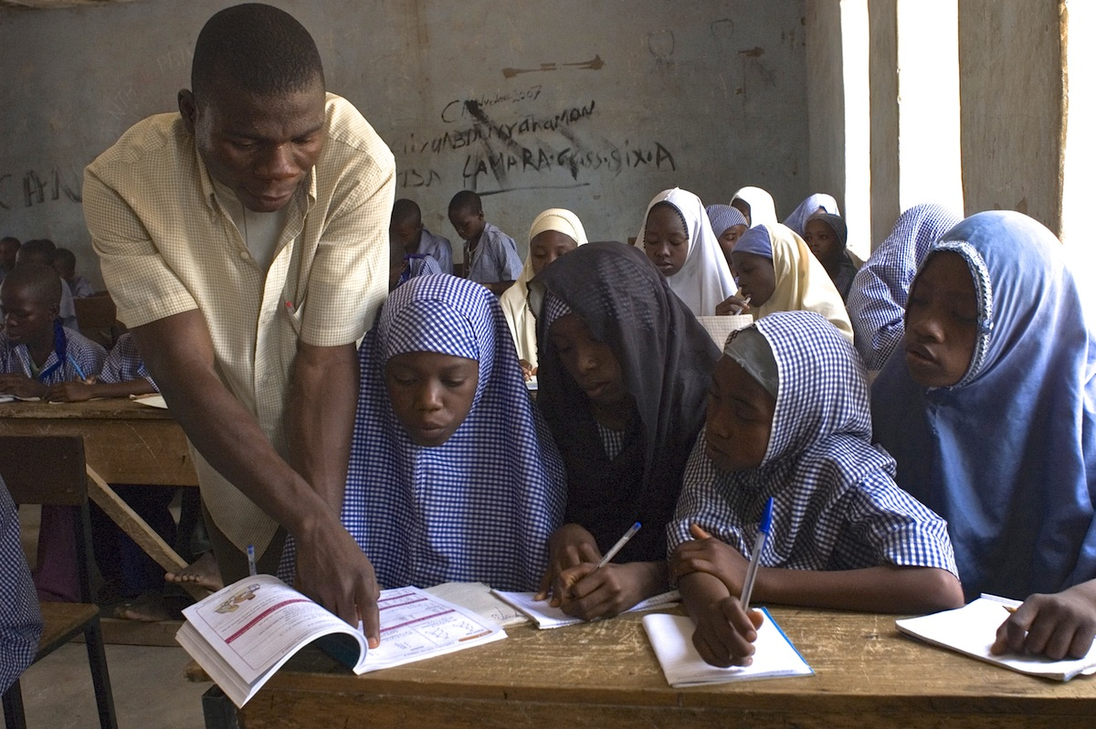 A teacher helps Hafsatu Garba, 13, while others watch, at the UNICEF-supported Konkiyel Primary School in Konkiyel Village in the northern Nigerian state of Bauchi.