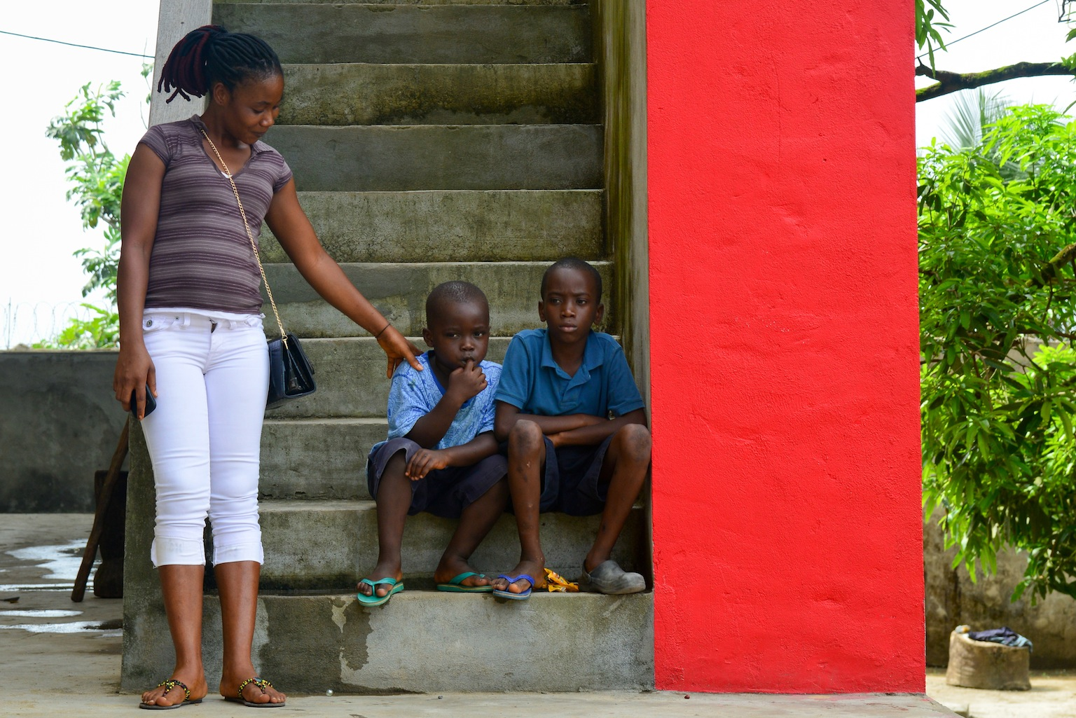 Caretaker Helen Morris consoles two boys who must remain in quarantine at an interim care center for children exposed to the Ebola virus, in Monrovia, Liberia.