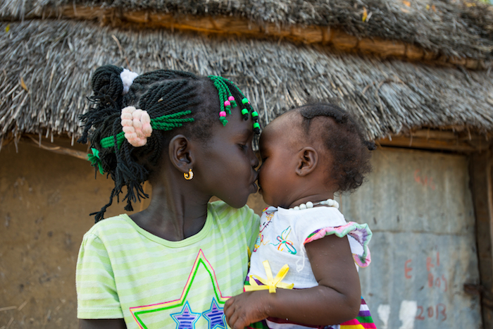 In October 2015, Nyayjaw, 8, kisses her baby sister Nyagua, whom she just met today, after being reunited with her mother in South Sudan. UNICEF helped reuinite the family after they were separated by conflict for two years.