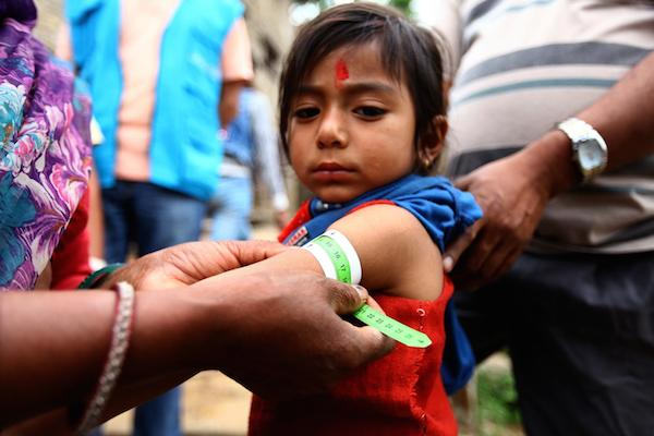 A volunteer measures a girl's upper-arm circumference to assess her nutrition status in Nepal's Dolakha District, the May 12th earthquake epicenter.