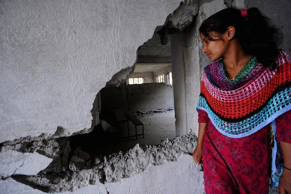 Laxmi Giri, whose home collapsed in the Nepal earthquake, looks into her destroyed classroom in Balefi