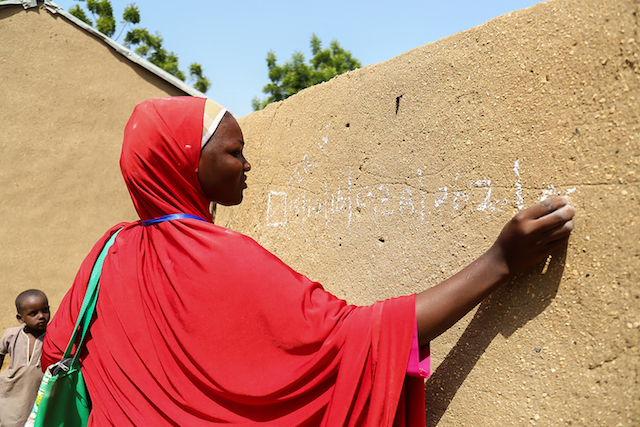 A member of a team of UNICEF volunteers records data in chalk on a wall noting the polio immunizations conductied in Tashan Damboa, a ward in Gwoza local government area in Borno State, Nigeria.