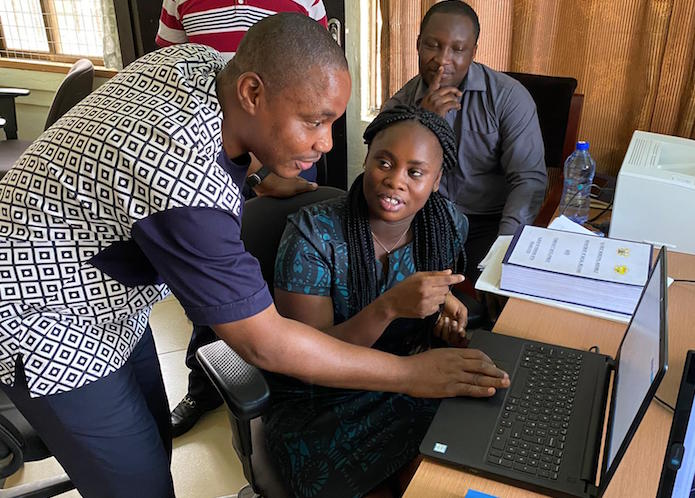 In Accra, Ghana, social worker Kingsley Agordo (far left, with colleagues) uses Primero, a case management system built by UNICEF and delivered by Microsoft, to locate and coordinate services for vulnerable children.