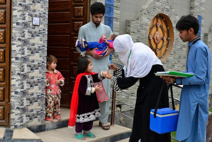 UNICEF-supported health workers and volunteers go door-to-door to vaccinate children against polio in the urban Peshawar, Pakistan.