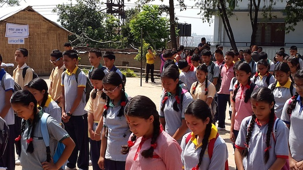 On their first day back to school, students at the Kuleshwor School in Kathmandu observe a moment of silence for Nepalis killed, injured, and missing since the earthquakes.