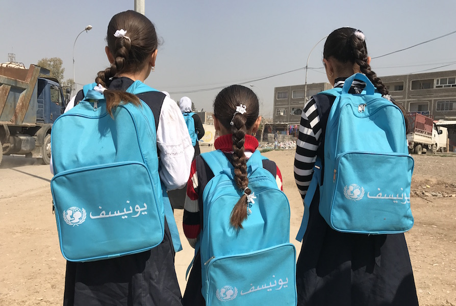 Girls with UNICEF-supplied backpacks return to school in Eastern Mosul, Iraq.