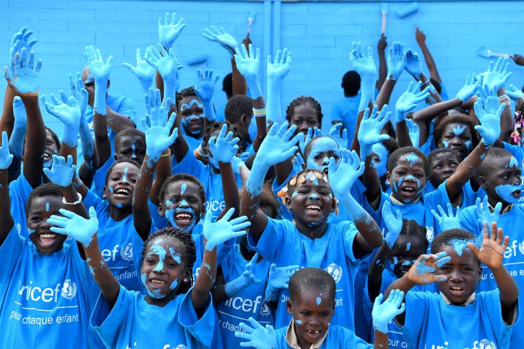 Children in Sakassou, Côte d'Ivoire, paint their new school, made out of recycled plastic bricks, blue to celebrate World Children's Day.