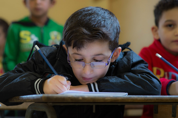 Lebanese and Syrian children study in double shifts at the UNICEF-supported Maalaka public boys school in Lebanon's Bekaa Valley. More than half the school's students are Syrian refugees.