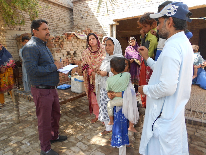 A UNICEF team member meets with community members in rural Pakistan to raise awareness about the importance of immunizations.