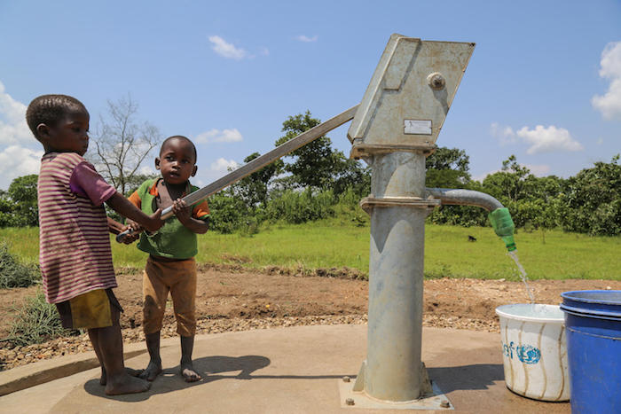 Three-year-old Innocent (right) and a friend use a new hand pump to drink clean water in Rutana Province, Burundi.