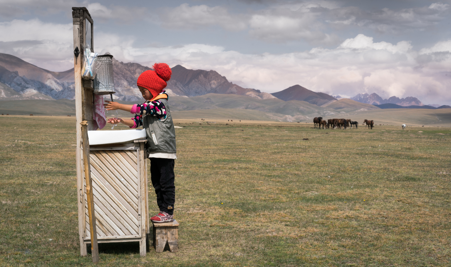 Five-year-old Ainazik demonstrates proper handwashing technique at an outdoor basin in a pasture in Naryn province, Kyrgyzstan.