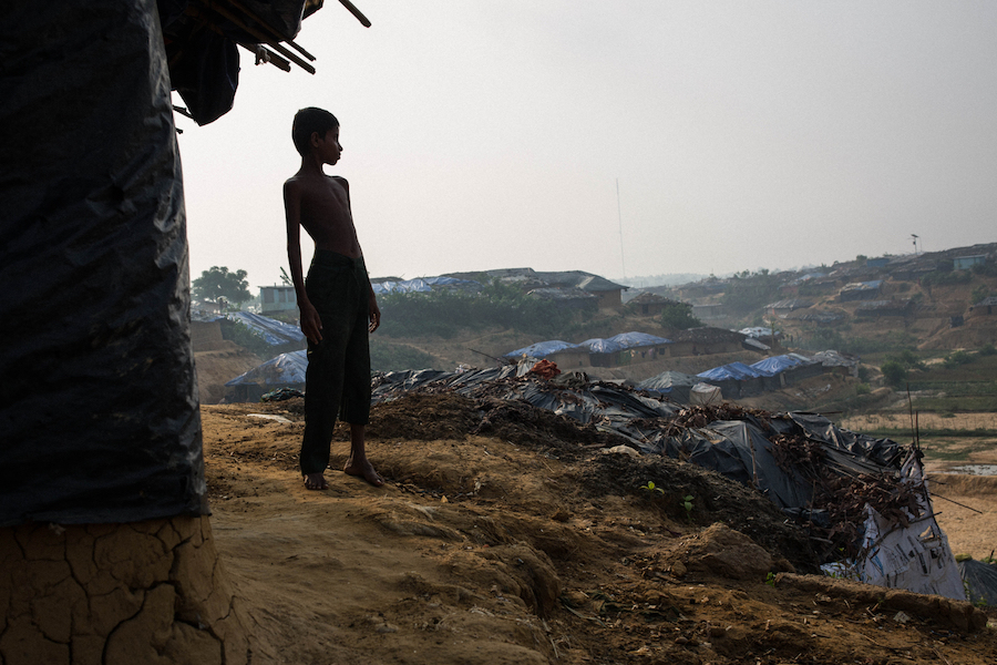 Omar, 8, stands outside the mud hut he shares with his parents and four siblings in Kutupalong Camp for Rohingya refugees in Bangladesh in May 2017.