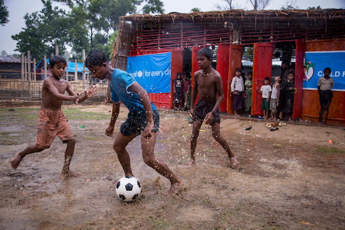 Rohingya children play in the rain outside a UNICEF-supported Child-Friendly Space in a refugee camp in Bangladesh after escaping horrific violence in neighboring Myanmar.
