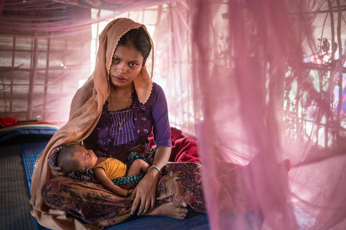 : Rohingya refugee Hazera Begum, 18, cradles her three-week-old after breastfeeding in a shelter she shares with her husband.
