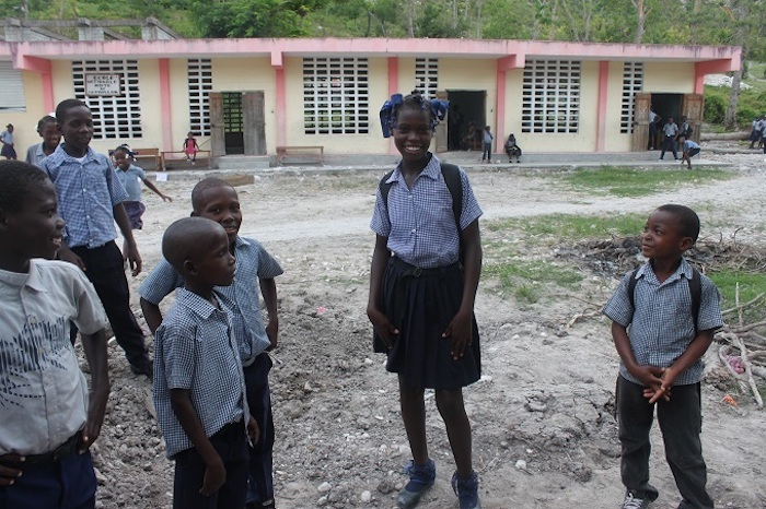 Thirteen-year-old Roseberline, center, was elated to return to her school after it was damaged by Hurricane Matthew and rebuilt with support from UNICEF.