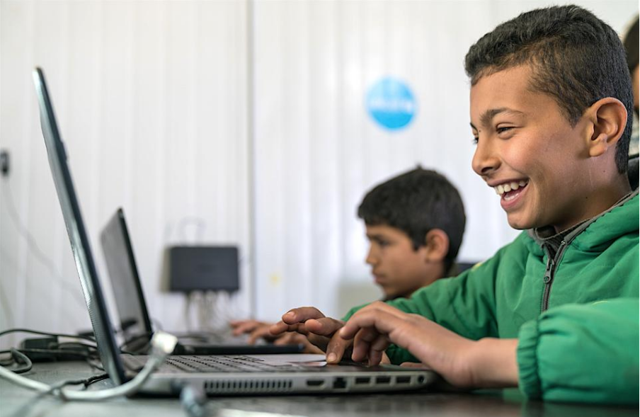 Bashar, 11, a Syrian child refugee living in the Za'atari Refugee camp in Jordan, uses a laptop in an educational program like those supported by the UNICEF USA Bridge Fund.